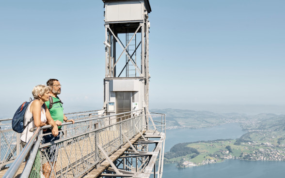 A man and woman are in hiking gear on the access platform in the lofty heights by Hammetschwand lift, enjoying the view of Lake Lucerne from their secure vantage point.